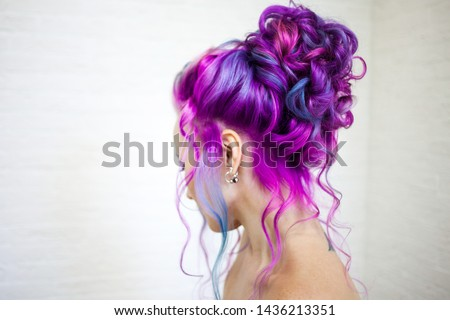 Portrait of a young beautiful woman with colored hair. Bright shades of blue and purple, gradient hair. Elegant hairstyle in the hairstyle salon