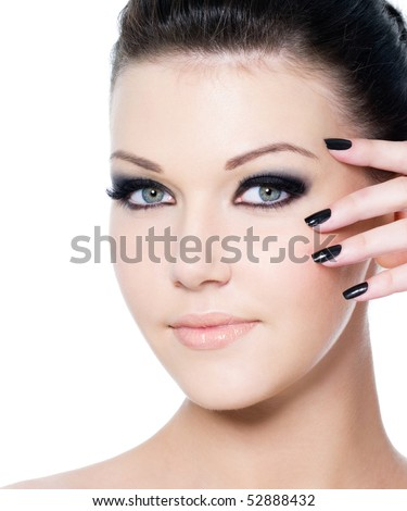 portrait of a young beautiful woman with fashion black make-up and manicure - isolated on white