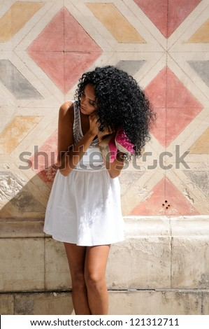 Portrait of a young black woman, afro hairstyle, getting dressed in the street - stock photo