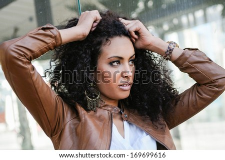 Portrait of a young black woman, afro hairstyle, in urban background