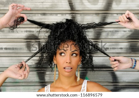 Portrait of a young black woman, afro hairstyle, in urban background with four hands playing with her hair