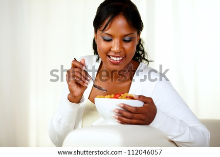 Portrait of a young black woman having healthy breakfast while is sitting on couch at home indoor