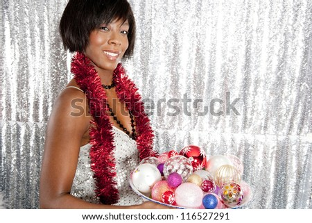 Portrait of a young black woman holding a dish full of Christmas bar balls tree decorations and wearing a strip of tinsel around her neck while standing in front of a silver sequins background.