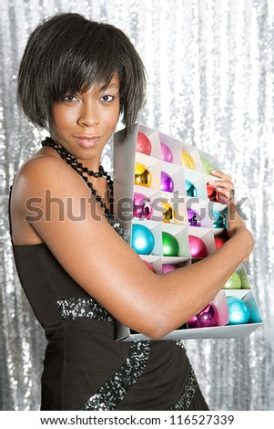 Portrait of a young black woman hugging a box with different color christmas balls decorations against a silver sequins background.