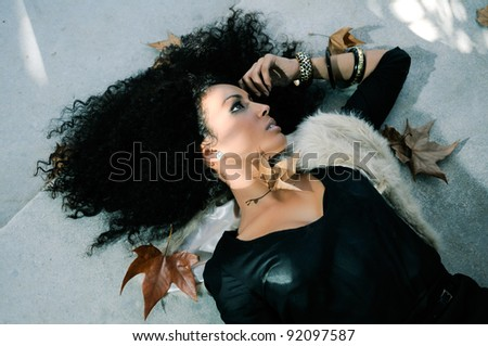 Portrait of a young black woman in the park with dry leaves - stock photo