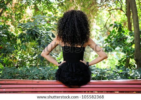 Portrait of a young black woman, model of fashion in a garden