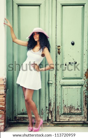 Portrait of a young black woman, model of fashion wearing dress and sun hat, with afro hairstyle