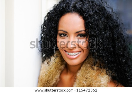 Portrait of a young black woman, model of fashion, wearing fur vest, with braces