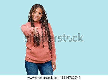 Shutterstock puzzlepix portrait of a young black woman wearing braids reaching out to greet someone or gesturing to help happy and excited m4hsunfo