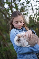 Portrait of a young blonde girl holding gently a pet bunny, rabbit in her arms outside in the garden.