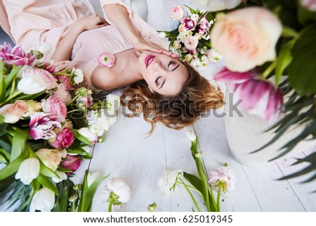 Portrait of a young blonde woman in flowers. Woman's face with make-up and hairstyle #625019345