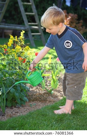 Portrait of a young boy watering the flowers in the garden - stock photo