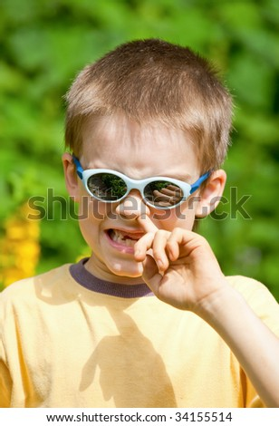 Portrait of a young boy wearing sunglasses picking his nose - stock photo