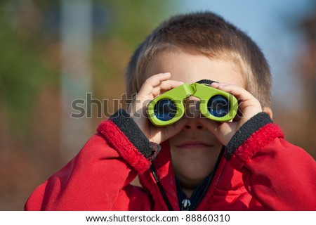Portrait of a young boy with binoculars. Front view.