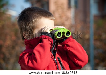 Portrait of a young boy with binoculars. Lateral view.