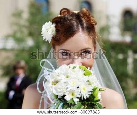 Portrait of a young bride in a white dress with a bouquet of flowers.
