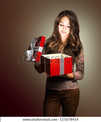 Portrait of a young brunette beauty with red gift box in creative lighting.