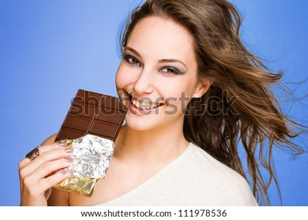 Portrait of a young brunette chocolate loving beauty on vibrant blue background.
