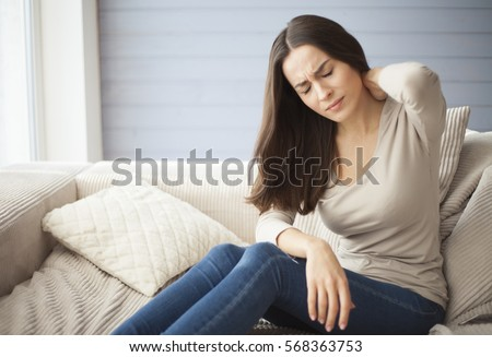 Portrait of a young brunette girl sitting on the couch at home with a headache and back pain.