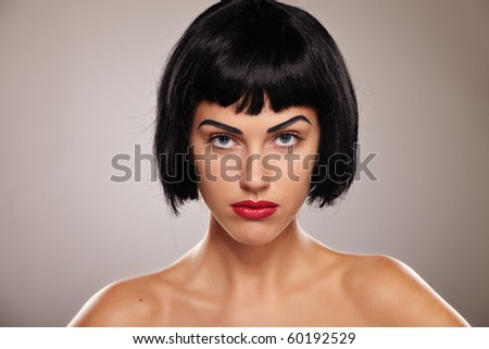 Portrait of a young brunette lady on grey background