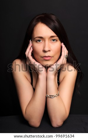 portrait of a young brunette  woman with arms crossed under her chin on dark black background