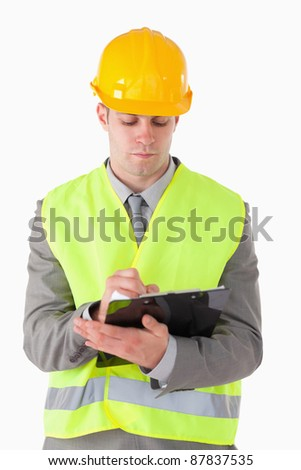Portrait of a young builder taking notes against a white background