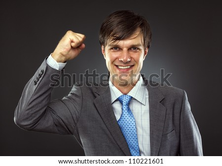 Portrait of a young business man enjoying success against a gray background