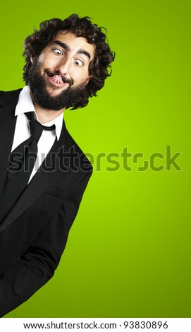 portrait of a young business man showing his tongue over a green background