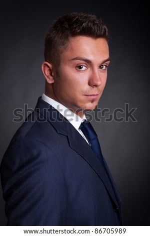 Portrait of a young business man, side profile on grungy background