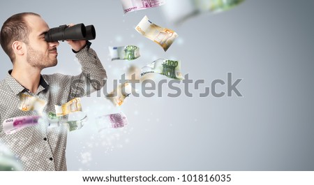 Portrait of a young business man with binoculars looking to the future. Money rain surrounding him
