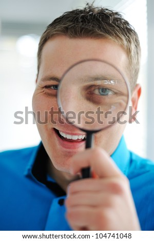 Portrait of a young business man with magnifying glass