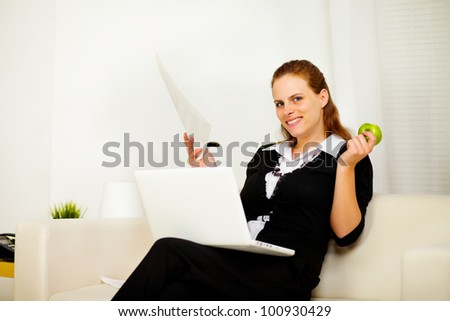 Portrait of a young business woman smiling and working at home while looking at you