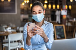 Portrait of a young business woman, wearing mask while talking on a mobile phone. Conceptual of new normal lifestyle during covid-19 pandemic.