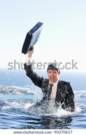 Portrait of a young businessman going out of the water with a briefcase in a swimming pool