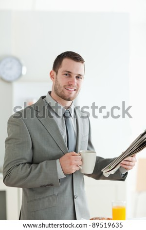 Portrait of a young businessman having breakfast while reading the news in his kitchen