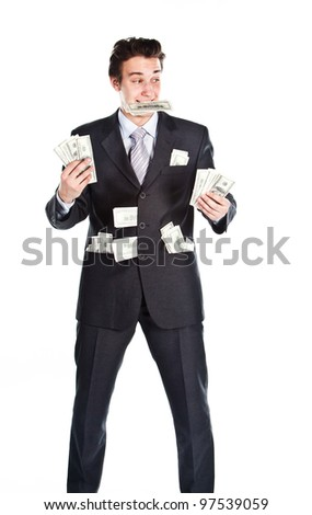 Portrait of a young businessman in a dark suit surrounded by flying dollar bills - stock photo