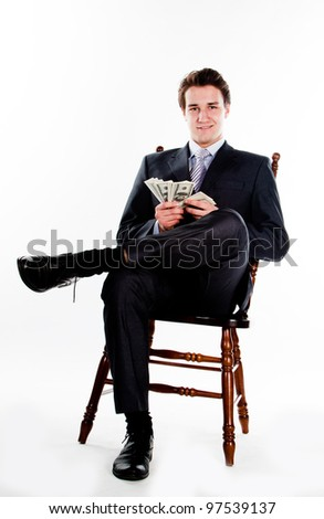 Portrait of a young businessman in a dark suit surrounded by flying dollar bills