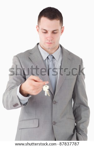 Portrait of a young businessman looking at a set of keys against a white background