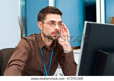 portrait of a young businessman looking at the monitor, he is concentrated on his job