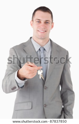 Portrait of a young businessman showing a set of keys against a white background