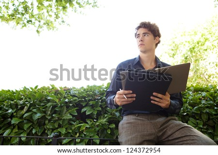 Portrait of a young businessman sitting in a city park writing notes and wearing a blue shirt.