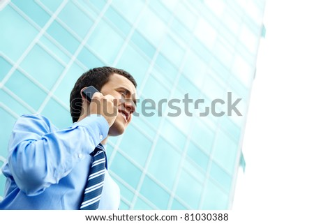 Portrait of a young businessman standing by office building and talking on the phone