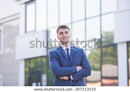Portrait of a young businessman standing over blurred background outdoors