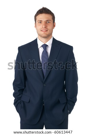 Portrait of a young businessman standing with his hands in the pockets.