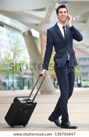 Portrait of a young businessman traveling with phone and bag