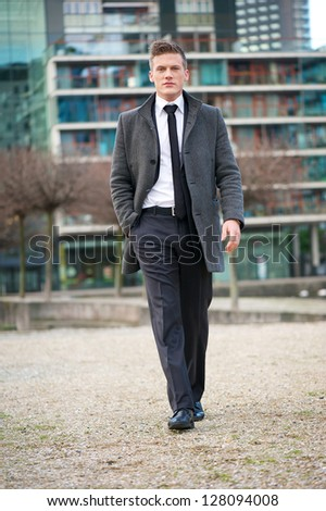 Portrait of a young businessman walking outdoors