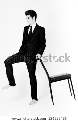 Portrait of a young businessman with a office chair, on white background