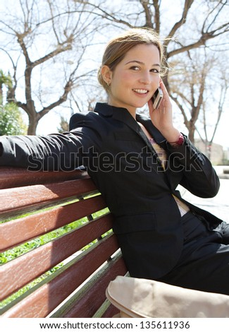 Portrait of a young businesswoman having a conversation using a smartphone on a phone call while sitting on a city park bench, smiling.