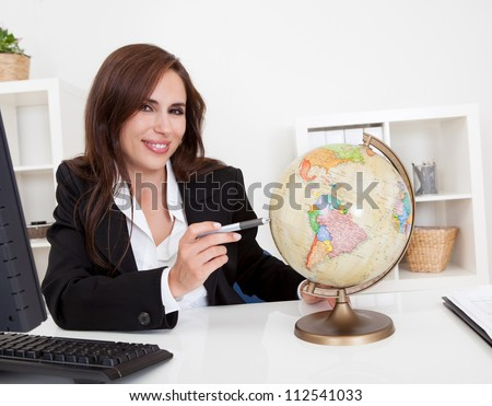 Portrait of a young businesswoman pointing at globe in office