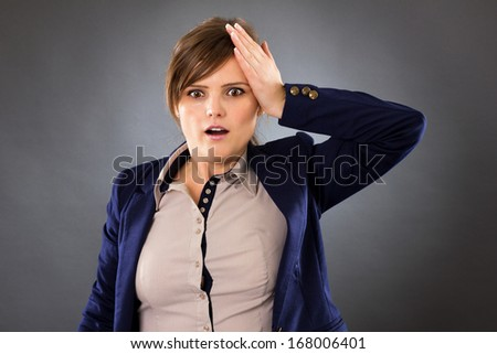 Portrait of a young businesswoman remembering something very important over gray background